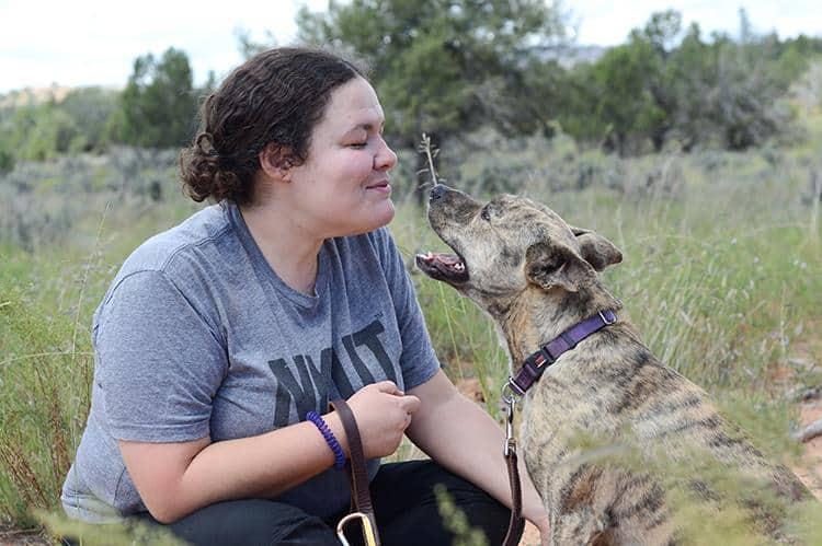 kneeling owner with dog speaking on